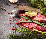 Raw beef steak. Preparation with old meat cleaver, butter and fresh herbs. On black stone background royalty free stock photos
