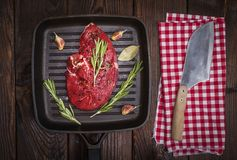 Raw beef steak. In spices on a black frying pan and knife , top view Stock Image