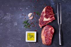 Raw beef steak. S and fork with spices on dark stone background with copy space Stock Photo