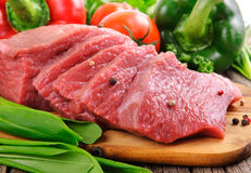Raw beef steak ready to cook. On a wooden board against the background of vegetables closeup Royalty Free Stock Photos