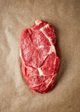 Raw beef steak on recycling paper, from above. Raw beef steak on recycling paper, top view royalty free stock images