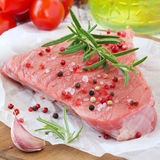 Raw beef steak. With red, black and white pepper beans, salt and fresh rosemary sprig ready to be cooked Royalty Free Stock Photo