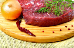 Raw beef steak. Raw beef steak with red pepper, herbs and onions on cutting board on wooden background Royalty Free Stock Photography