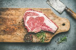Raw beef steak rib-eye on board with seasoning and knife Stock Photo