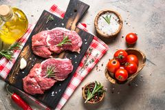 Raw beef steak rib eye with cooking ingredients. Raw meat. Raw beef steak rib eye on a cutting board with rosemary and spices. Top view copy space Royalty Free Stock Image