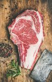 Raw beef steak rib-eye with seasoning and knife, wooden background