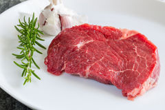 Raw beef steak with rosemary and garlic.  Stock Photography