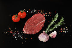 Raw beef steak. Steak seasoned with pepper and salt on a black background. Young garlic, pepper and rosemary. Top view Royalty Free Stock Photos