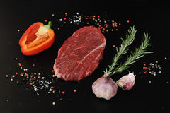 Raw beef steak. Steak seasoned with pepper and salt on a black background. Young garlic, pepper and rosemary. Top view Royalty Free Stock Image