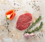 Raw beef steak. Steak seasoned with pepper and salt on a marble countertop. Young garlic, pepper and rosemary. Top view Stock Photo