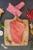Raw beef steak with seasoning and herbs Royalty Free Stock Photos