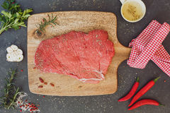 Raw beef steak with seasoning. Raw beef steak seasoned with salt and pepper, top view Royalty Free Stock Photo
