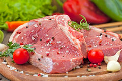 Raw beef steak with spice. And vegetables Royalty Free Stock Photos