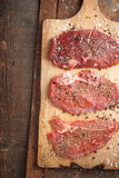 Raw beef steak and spicel on cutting board on the table. Vertical Royalty Free Stock Photo
