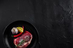 Raw beef steak in spices on a black frying pan for grilling, top view. Still life. Copy space. Flat lay Royalty Free Stock Photography