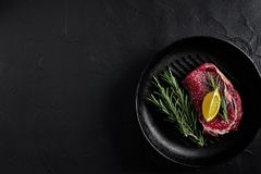 Raw beef steak in spices on a black frying pan for grilling, top view. Still life. Copy space. Flat lay Stock Images