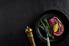 Raw beef steak in spices on a black frying pan for grilling, top view. Still life. Copy space. Flat lay Stock Photos