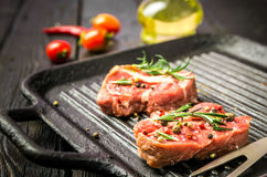 Raw beef steak and spices. Beef steak on the grill pan with spices and tomatoes Stock Images
