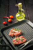 Raw beef steak and spices. Beef steak on the grill pan with spices and tomatoes Royalty Free Stock Images