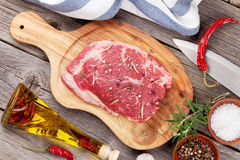 Raw beef steak with spices and herbs. On wooden table. Top view Stock Images