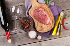 Raw beef steak with spices and herbs. On wooden table. Top view Stock Photography