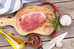 Raw beef steak with spices and herbs. On wooden table. Top view Stock Photos