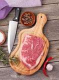 Raw beef steak with spices and herbs. On wooden table. Top view Royalty Free Stock Images