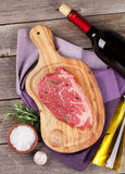 Raw beef steak with spices and herbs. On wooden table. Top view Stock Photo