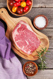 Raw beef steak with spices and herbs. On wooden table. Top view Royalty Free Stock Photo