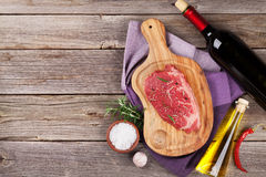 Raw beef steak with spices and herbs. On wooden table. Top view with copy space Stock Photography