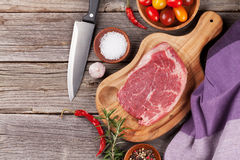 Raw beef steak with spices and herbs. On wooden table. Top view with copy space Stock Image
