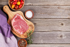 Raw beef steak with spices and herbs. On wooden table. Top view with copy space Stock Photos