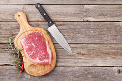 Raw beef steak with spices and herbs. On wooden table. Top view with copy space Royalty Free Stock Photos