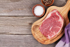 Raw beef steak with spices and herbs. On wooden table. Top view with copy space Royalty Free Stock Images