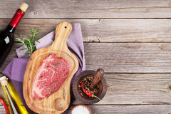 Raw beef steak with spices and herbs. On wooden table. Top view with copy space Stock Images