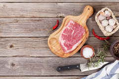 Raw beef steak with spices and herbs. On wooden table. Top view with copy space Royalty Free Stock Photography