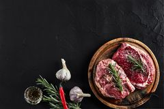 Raw beef steak with spices and ingredients for cooking on cutting board and slate background. Top view. Still life. Copy space. Flat lay Stock Photos