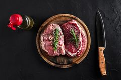 Raw beef steak with spices and ingredients for cooking on cutting board and slate background. Top view. Still life. Copy space. Flat lay Royalty Free Stock Image