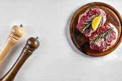 Raw beef steak with spices and ingredients for cooking on wooden cutting board and white background. Top view. Copy space. Still life. Flat lay Stock Photos