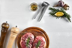 Raw beef steak with spices and ingredients for cooking on wooden cutting board and white background. Top view. Copy space. Still life. Flat lay Royalty Free Stock Photos