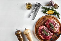 Raw beef steak with spices and ingredients for cooking on wooden cutting board and white background. Top view. Copy space. Still life. Flat lay Stock Images