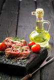 Raw beef steak and spices. Raw steak on the old board sprinkled with spices Stock Photos