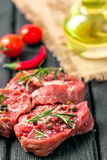 Raw beef steak and spices. Raw steak on the old board sprinkled with spices Stock Images