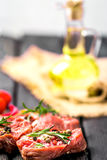 Raw beef steak and spices. Raw steak on the old board sprinkled with spices Stock Image
