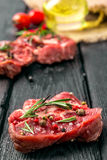 Raw beef steak and spices. Raw steak on the old board sprinkled with spices Royalty Free Stock Photography
