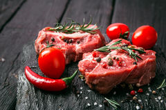 Raw beef steak and spices. Raw steak on the old board sprinkled with spices Stock Photography