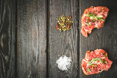 Raw beef steak and spices. Raw steak on the old board sprinkled with spices Royalty Free Stock Photo