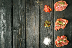 Raw beef steak and spices. Raw steak on the old board sprinkled with spices Royalty Free Stock Photos