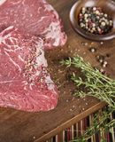 Raw beef steak with spices. Raw beef steak with herbs and spices royalty free stock image