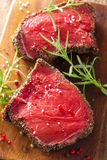 Raw beef steak with spices and rosemary on wooden background Royalty Free Stock Photos